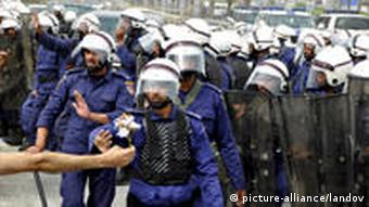 Bahraini anti-government protesters demonstrate in front of riot police on an overpass near Pearl roundabout Sunday, March 13, 2011, in Manama, Bahrain.