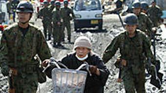 Drei Polizisten begleiten eine alte Frau mit Fahrrad im Katastrophengebiet (Foto: AP)