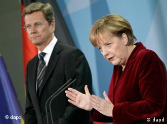 Angela Merkel gestures during her address, Guido Westerwelle stands next to her