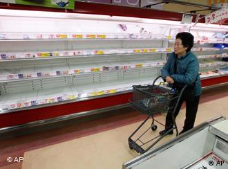 A shopper looks at the empty shelves in a supermarket in Moriyama, Japan, Tuesday, March 15, 2011, four days after a giant quake and tsunami struck the country's northeastern coast. (AP Photo/Mark Baker)