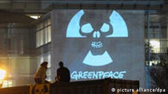 Zwei Greenpeace-Aktivisten vor dem auf das Bundeskanzleramt in Berlin projizierten als Totenkopf gestalteten Anti-Atomkraft-Symbol (Foto: Soeren Stache dpa/lbn)
