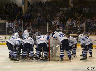 Huskies gather around the net before the opening face-off