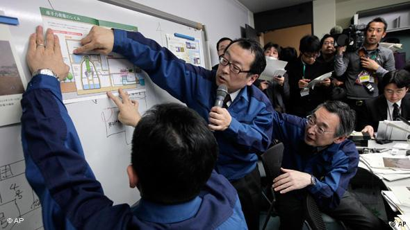 Tokyo Electric Power Co. employees explains the situation at the Fukushima nuclear complex