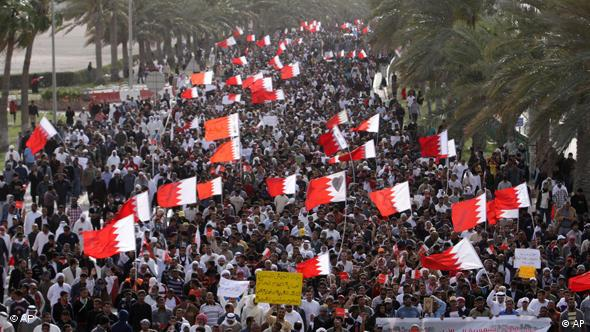 Thousands of anti-government protesters march Tuesday, March 15, 2011, to the Saudi embassy in Manama, Bahrain. Frenzied clashes swept Bahrain Tuesday, a day after a Saudi-led military force entered the country to defend its Sunni monarchy from a Shiite-led protest movement. Hundreds of demonstrators were injured by shotgun blasts and clubs, a doctor said. The yellow sign center foreground reads: The Saudi army came to protect the illegitimate government, not the aggrieved, legitimate nation and the banner at right says: The Saudi army's entry to Bahrain is an occupation we will never accept. (AP Photo/Hasan Jamali)