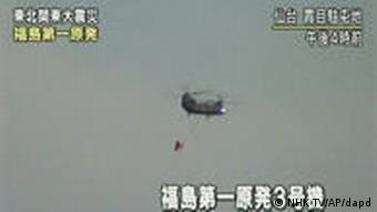 A helicopter with a bag of water over Fukushima