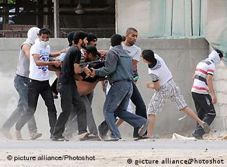 (110315) -- MANAMA, March 15, 2011 () -- Protestors carry an injured man during a clash with police in the suburbs of Manama, Bahrain, March 15, 2011. Bahraini King Hamad bin Isa al- Khalifa declared on Tuesday the state of emergency in the tiny Gulf nation for three months to deal with unrest and protests which swept the country several weeks ago, the official TV said. () (zw)