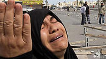 A Bahraini woman reacts, as young men and men wait in the streets behind her for government forces they expect will role into their Shiite Muslim village of Dumistan, Bahrain, southwest of the capital of Manama, Wednesday, March 16, 2011. Soldiers and riot police used tear gas and armored vehicles to drive out hundreds of anti-government protesters occupying a landmark square in Bahrain's capital, a day after emergency rule was imposed in the violence-wracked Gulf kingdom. (Foto:Hasan Jamali/AP/dapd)