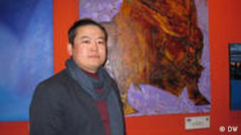 Mongolian artist A. Chadraabal standing in front of one of his paintings