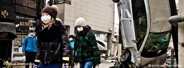 Japanese Women are wearing masks and carry plastic bags containing bottles as they walk in a devastated area in the town of Kamaishi