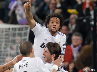 Real Madrid's Marcelo of Brazil, top, celebrates after scoring against Lyon