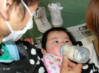 A nine-month-old girl drinks milk at an evacuation center in Ofunat, Japan