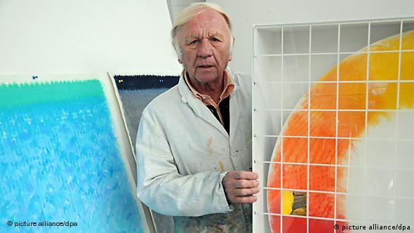 Der Maler Heinz Mack steht in weißem Kittel vor seinen farbigen Bidlern.