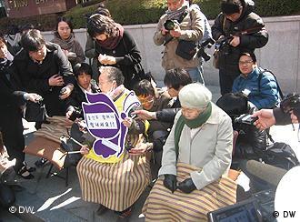 Bild wurde von Jason Strother in Seoul, Südkorea bei einer Demonstration vor der japanischen Botschaft aufgenommen. Die ehemalige Trostfrauen demonstrieren regelmäßig gegen die Zwangsprostitution, die japanische Soldaten während des zweiten Weltkrieges erzwungen. In diesem Foto vom 16.03.11 nehmen die Frauen trotz der Grausamkeiten vom der Zeit der Zwangsprostitution, Schweigeminuten, um Japan in seiner jetztigen Not zu bedenken. Die Frauen heißen Kil Won Ok und Lee Ok Seong