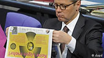 Norbert Röttgen, reading a newspaper with a nuclear logo