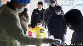People wait to receive a radiation exposure scanning in Fukushima