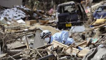 A firefighter conducts a search operation amid rubble in northern Japan