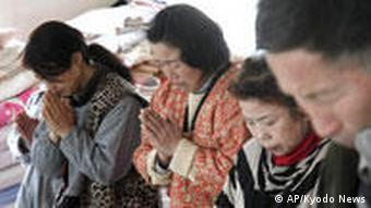 People remember the victims of the earthquake and tsunami in a moment of silence