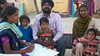 An enumerator taking down information from a family in Punjab