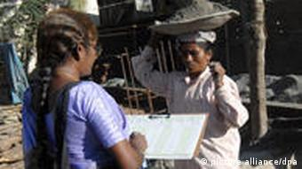 A Tamil Nadu Census official stops a female construction worker to question her about housing details