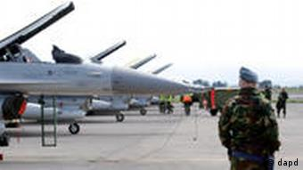Danish airforce personnel stand on the tarmac next to F-16 aircrafts at the Nato airbase in Sigonella, on the southern Italian Sicily island, Sunday, March 20, 2011.