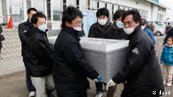 A coffin is carried from a temporary morgue at a bowling alley in Natori, Miyagi Prefecture, Monday, March 21, 2011 as the death toll continues to rise following the March 11 earthquake and tsunami that devastated the northeast coast of Japan. (Foto:Mark Baker/AP/dapd)