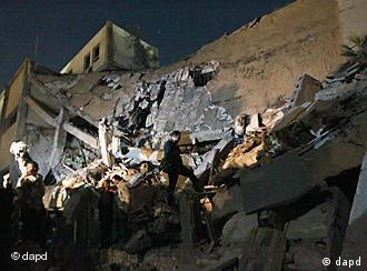Soldiers survey the damage to an administrative building after an air strike on March 21, 2011