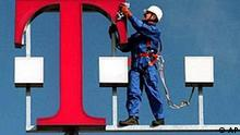 A worker cleans the logo of Deutsche Telekom on top of the Bremen, northern Germany, telephone exchange on this Oct. 2, 1996 file photo. Deutsche Telekom, Europe's biggest phone company, said Wednesday, Oct. 2, 2002, it is accelerating a program to cut nearly 30,000 jobs by 2005 to restore its earnings. (AP Photo/Joerg Sarbach/fls)