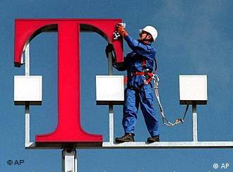 A worker cleans the logo of Deutsche Telekom