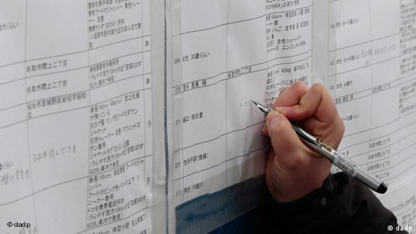 An official updates a list of the dead outside a temporary morgue in Miyagi Prefecture