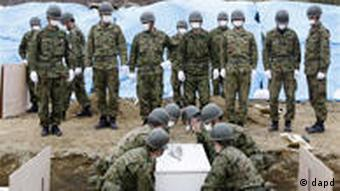 Japan Ground Self-Defense Force lay a coffin during a burial ceremony for tsunami victims