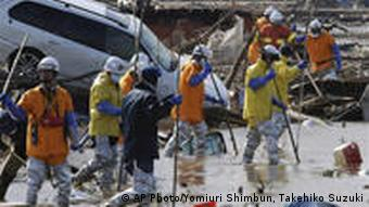 Firefighters and others search for missing persons in the March 11 earthquake and tsunami-destroyed city of Sendai, northern Japan Wednesday, March 23, 2011. (AP Photo/Yomiuri Shimbun, Takehiko Suzuki) JAPAN OUT, MANDATORY CREDIT