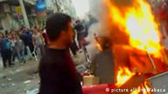 A protester in the street with an object burning near to him