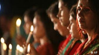 Women holding a candle light vigil to mark the killing of thousands of unarmed Bengalis