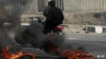 An anti-government protester runs past a burning tyre in Daraa