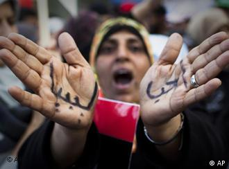 A Libyan woman reacts with her hands written on them in Arabic I love Libya' as she joins a rally in support of the allied air campaigns against the forces of Moammar Gadhafi in Benghazi, eastern Libya, Wednesday, March 23, 2011