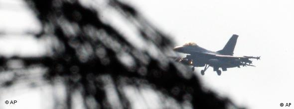 A Danish F-16 is seen behind barbed wire as it lands at the Sigonella airbase, southern Italy, March 23