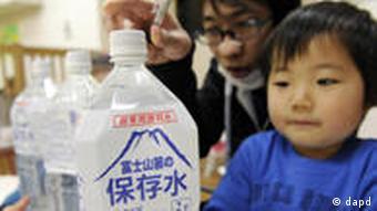 Ein Kind in Tokio schaut auf eine Flasche Wasser (Foto: dapd)