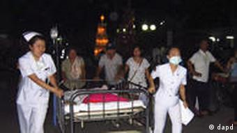 Nurses evacuating patients from a building at Chiang Rai hospital, Thailand following strong aftershocks