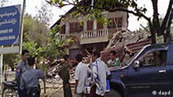 Officials stand in front of a building destroyed by an earthquake that hit Myanmar on Thursday, March 24