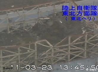 In this image taken from footage filmed on Wednesday, March 23, 2011 by Japan Ground Self-Defense Force and released by the Japan Defense Ministry Friday, March 25, the damaged roof of Unit 1 of the tsunami-stricken Fukushima Dai-ichi nuclear complex is seen. Japanese reads: Ground Self-Defense Force troop in charge of Japan's northeastern region (Northeastern helicopter). (Foto:Japan Defense Ministry/AP/dapd) EDITORIAL USE ONLY