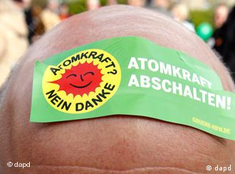 protester with sticker reading 'Switch off nuclear energy' on his head