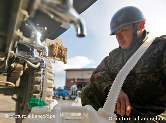 A Japanese soldier fills up a tank with tap water from a water truck in the tsunami-hit coastal city of Kesennuma