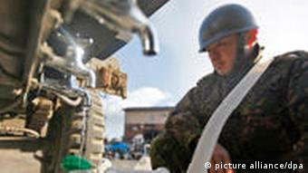A Japanese soldier fills up a tank with tap water from a water truck