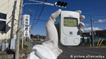 Eine weiße Hand hält einen weißen Geigerzähler in die Luft (Foto: picture-alliance/dpa)