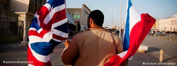 Fuerzas anti-Gadafi sostienen banderas británica y francesa en Bengasi.