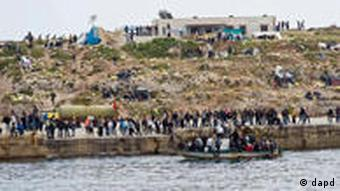 Migrants on a boat approach the Lampedusa harbor, Italy, Monday, March 28, 2011. Fishermen have used empty migrants' boats to block the entrance to Lampedusa harbor, a mostly symbolic act which still raised cheers from townsfolk gathered on the quays. News reports Monday said the boats, which had been seized by Italian authorities, were used to block the tiny island's port. Officials reported 460 migrants arrived from North Africa overnight, joining 3,000 more who have arrived in the last three days and escalating tensions on the island, closer to Africa than to mainland Italy. (Foto:AP/dapd)
