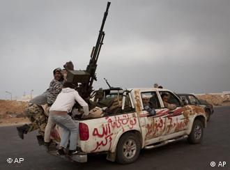 Libyan rebels jump onto the back of their vehicle as they leave Ras Lanouf, 250 km east of Sirte, central Libya, Tuesday, March 29, 2011. Gadhafi's forces drove the rebels out of Bin Jawwad, a hamlet east of Sirte, on Tuesday. Cars and trucks of the retreating rebels filled both lanes of the highway east to the oil port of Ras Lanouf. (AP Photo/Anja Niedringhaus