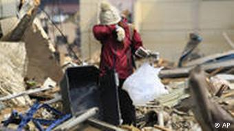 A woman cries in the rubble of a house