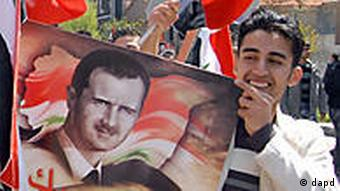 Supporter of President Bashar Assad holds a poster of Assad