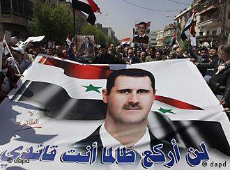 pro-assad protesters carrying a banner